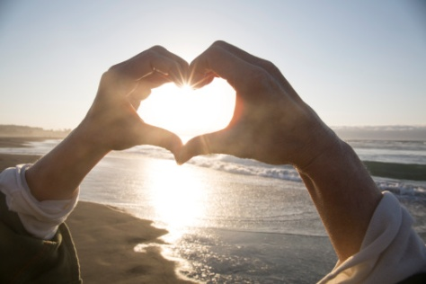 xc466305813-womans-hands-create-heart-shape-above-ocean-gettyimages